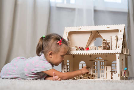 girl of four years playing with a dollhouse