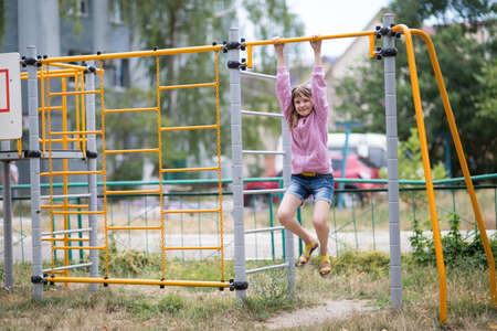A teenage girl is engaged in childrens exercise equipment, a girl of thirteen years is engaged in sports