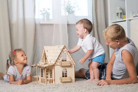 Children play in a room with a doll house Stock Photo