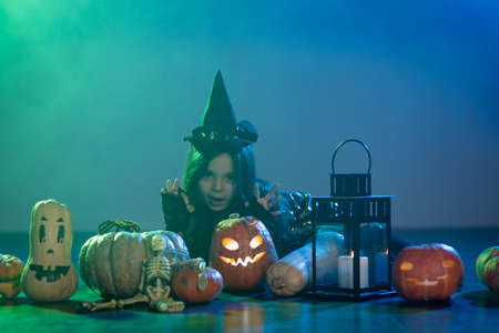 Baby girl in a witch costume for Halloween with a pumpkin