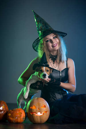 Young woman in a witch costume with a dog