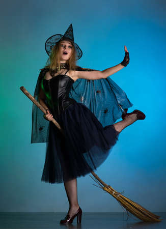Young woman witch conjures, woman in costume on halloween Standard-Bild