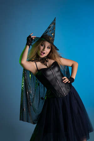 Young woman witch conjures, woman in costume on halloween Foto de archivo