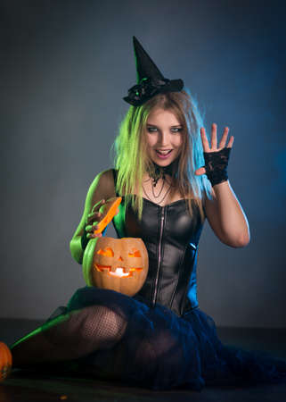 Young woman witch conjures, woman in costume on halloween Banque d'images