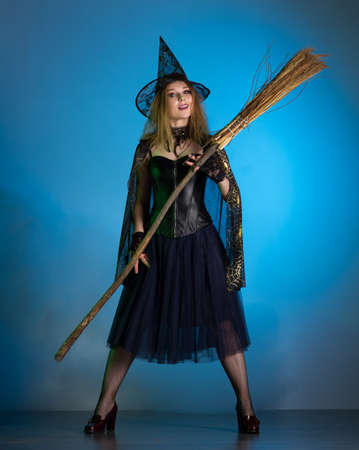 Young woman witch conjures, woman in costume on halloween Banco de Imagens