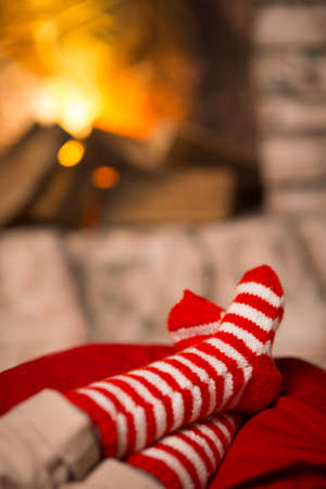 feet of the child in striped socks are heated near the fireplace