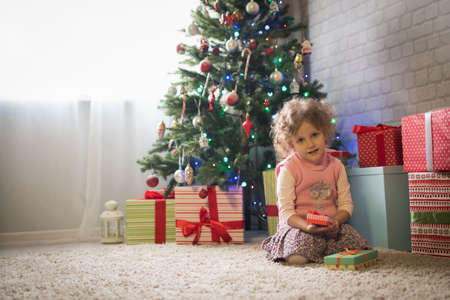 Girl sitting near the Christmas tree