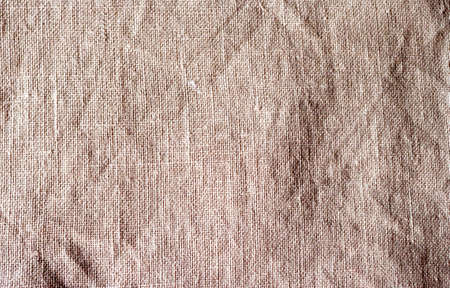 The texture of a crumpled natural linen beige grey color fabric background. Weaved texture of cotton linen towels, wash cloth, kitchen towel, hand towel, bath towels background. Blank linen color background for layouts.
