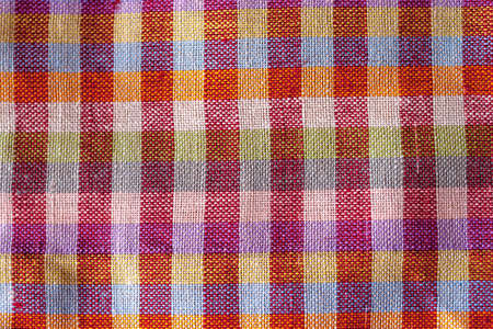 The texture of a crumpled colorful red violet multycolor fabric background. Weaved waffle texture of cotton linen towels, wash cloth, kitchen towel, hand towel, bath towels background. Blank bright multycolor background for layouts.