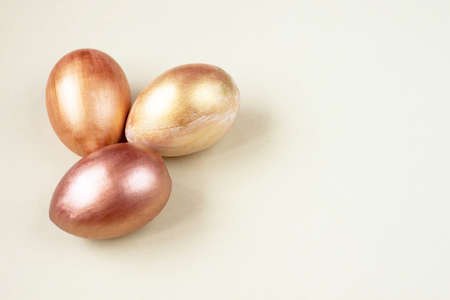 Three gold and bronze eggs on a white background