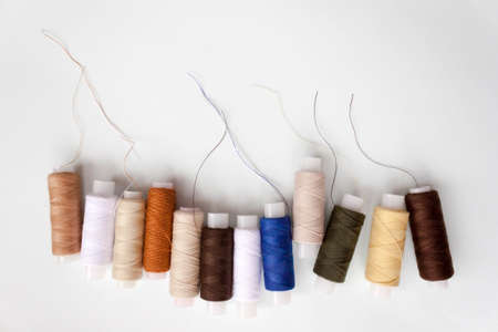 Row of number of different colors colorful multicolored sewing thread spools on light blue background. Selective soft focus, copy space for text. 写真素材