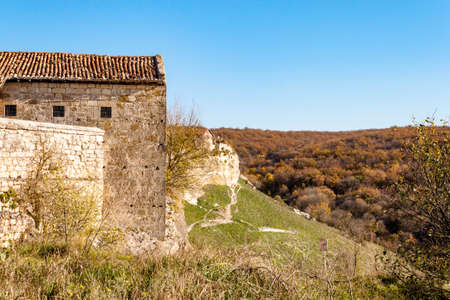 Old stone houses and walls of Medieval cave city-fortress Chufut-Kale in the mountains, Bakhchisaray, Crimea on landscape view background of blue sky and autumn fall sunny greens 写真素材 - 134643121