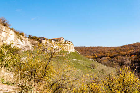 Old stone houses and walls of Medieval cave city-fortress Chufut-Kale in the mountains, Bakhchisaray, Crimea on landscape view background of blue sky and autumn fall sunny greens