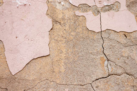 Beautiful background of rough rustic texture the shabby Old ruined wall of the historic building with pink cracked plaster and cement