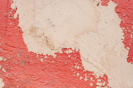 Beautiful background of rough rustic texture the shabby Old ruined wall of the historic building with pink orange salmon cracked plaster with cement patch Stockfoto