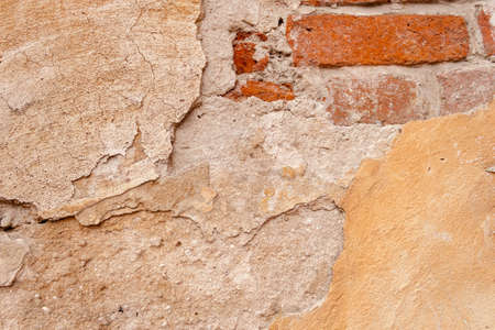 Beautiful background of rough rustic texture the shabby Old ruined wall of the historic building with yellow cracked plaster through which the old Vintage red aged brick shines through.
