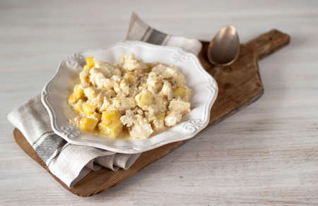 Bacalhau com natas Portuguese cuisine Traditional Portugal dish baked cod with potatoes, onions and cream in white porcelain plate on cutting Board on napkin in rustic style. Selective soft fokus