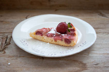 Piece of round strawberry berries tart pie pudding on white plate on rustic wooden background. Side view