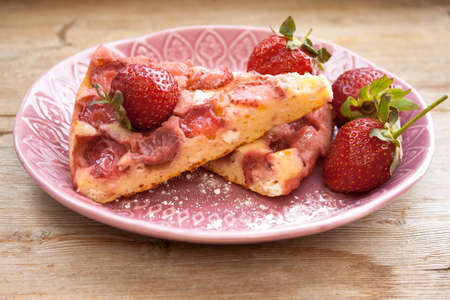 Piece of round strawberry berries tart pie pudding on pink plate on rustic wooden background. Side view
