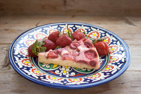 Piece of round strawberry berries tart pie pudding on plate with Oriental blue patternon rustic wooden background. Side view 版權商用圖片