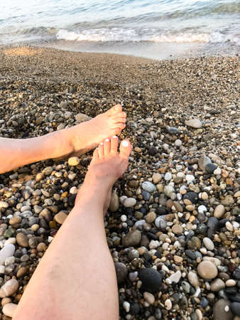Close-up of woman and men legs feet on the rocky beach against the sea shore background. Rest, vacation, love concept