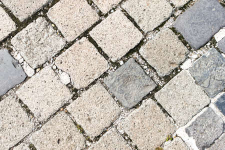 Old stone road texture . regular rows of granite paving stones background. Granite cobblestone pavement pattern closeup view