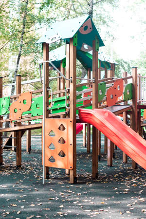Wooden childrens outdoor playground equipment slide red, orange and green color on natural trees background view. Stock Photo