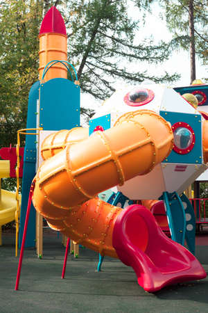 Plastic children outdoor playground equipment slide red, orange and blue color on natural trees background view.