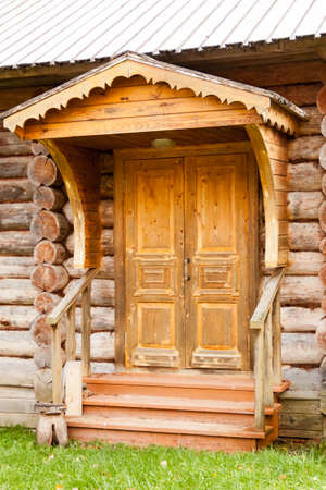 Wooden porch entrance door with architectural decorative elements wood carving of old Russian house Foto de archivo - 131851116