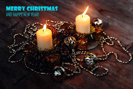 Lighted candles in candle holders with pine cones, tinsel, decorative toy balls and garland on wooden background in dark colors. Merry Christmas Greeting Card wallpaper. New Year winter decor concept. Stockfoto