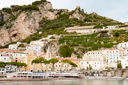 AMALFI, ITALY NOVEMBER 7 2019: mountainside with a Amalfi on Tyrrhenian sea landscape sunset city and nature panoramic view. Houses and hotels, church and cemetery