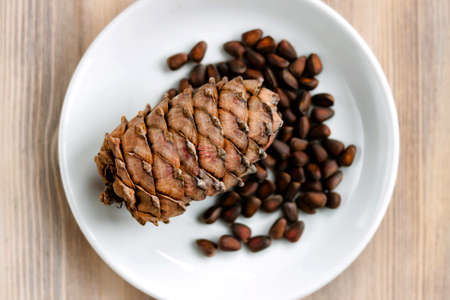 Pine cone and nuts on white plate on natural light whitewashed wooden background. The concept of healthy eating organic food, vegetarian. Top view. Selective soft focus. Shallow depth of field. Text c