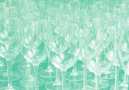 Close up rows of empty wine glasses on colored background in color 2020. Green color trend by 2020