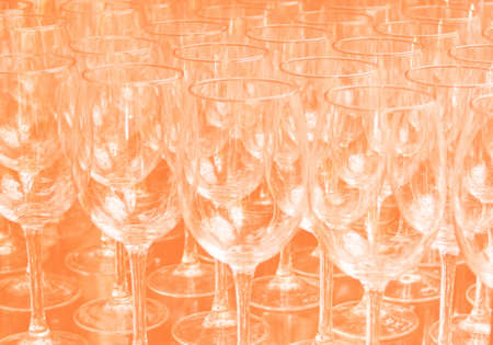 Close up rows of empty wine glasses on colored background in color 2020. Orange color trend by 2020 写真素材