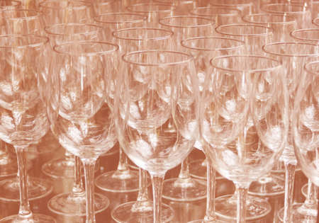 Close up rows of empty wine glasses on colored background in color 2020. Brown color trend by 2020