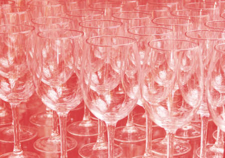 Close up rows of empty wine glasses on colored background in color 2020. The red color trend by 2020 写真素材