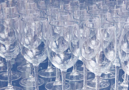 Close up rows of empty wine glasses on colored background in color 2020. Blue color trend by 2020