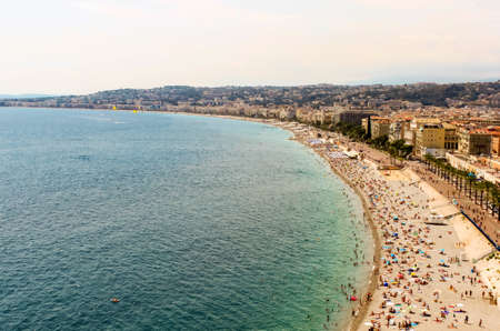 NICE, FRANCE - AUGUST 6, 2019 - Beautiful beach Promenade des Anglais in old city center of Nice. Natural background view. Mediterranean tourist destination, French riviera, Cote dazur, Europe.