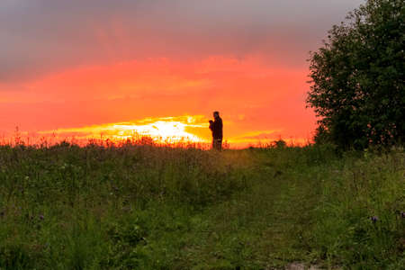Silhouette of a man person holding a dog pug on beautiful natural background view against sundown. Dramatic sunset in nature concept. Text copy space.