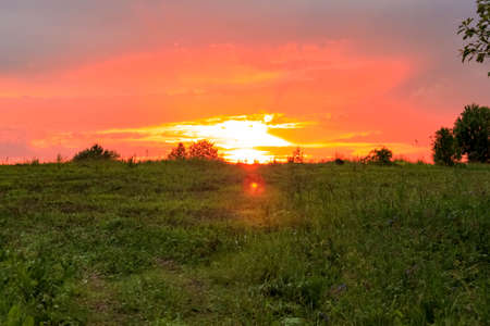 Dramatic sunset in nature concept. Country road through the green field beautiful natural background view against sundown. Text copy space. 写真素材