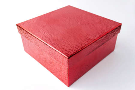 Single red color gift paper cardboard leather embossed box on white background. Holyday present concept. Close up view. Selective soft focus. Text copy space.