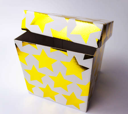 Single white color golden starred gift paper cardboard box on light background. Holyday present concept. Close up view. Selective soft focus. Text copy space.