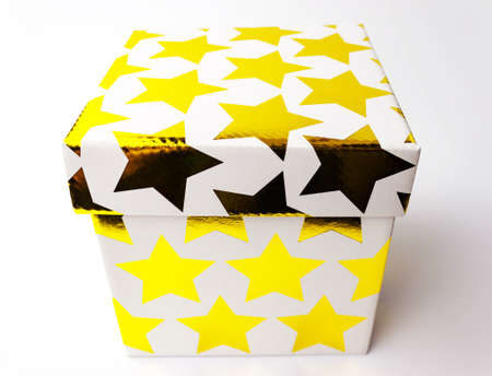 Single white color golden starred gift paper cardboard box on white background. Holyday present concept. Close up view. Selective soft focus. Text copy space. 写真素材