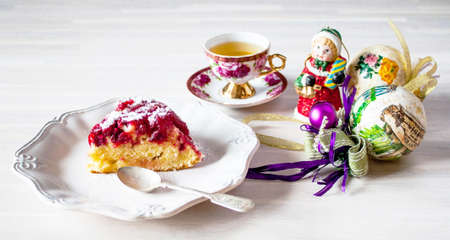 Piece of round cranberry tart pie cake on white plate on old wooden table background with christmas new year decoration close up view. Selective focus. Christmas New Year cake concept 写真素材