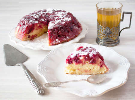 Cranberry tart pie cake, white ceramic plate, tea spoon, tea glass, cup holder, cooking spatula close up on white wooden table backgound view. Selective focus. Christmas New Year cake concept 写真素材
