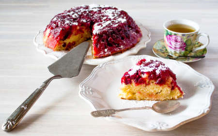 Cranberry tart, pie, cake piece, powdered sugar, white ceramic plate, tea spoon, cup of tea. Close up on white wooden table backgound view. Selective focus. Copy space. Christmas New Year cake concept