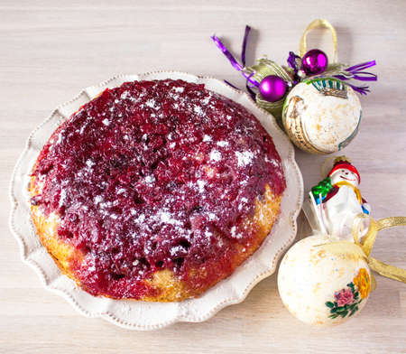 Whole round cranberry tart pie cake on white plate on wooden table background with christmas new year decoration close up view. Selective focus. Christmas New Year cake concept