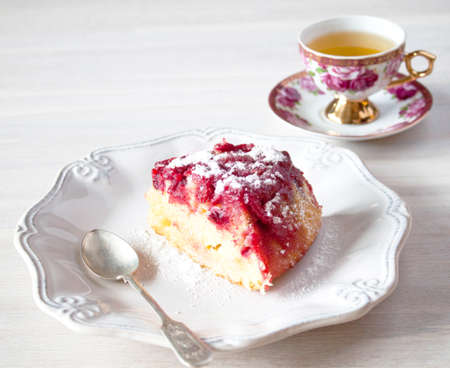Cranberry tart, pie, cake piece on white ceramic plate, tea spoon, cup of tea. close up on white wooden table backgound view. Selective focus. Copy space. Christmas New Year cake concept