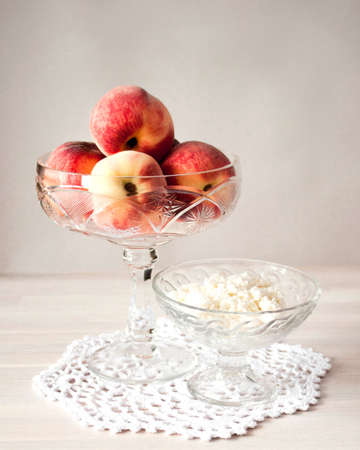 Ripe whole peaches and hommade cottage cheese in cristal bowls on white table background. Selective soft focus. Text copy space. Healthy breakfast concept 写真素材