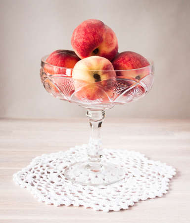 Ripe whole peaches on cristal bowl on white table background. Selective soft focus. Text copy space. Harvesting, healthy food, fresh fruit concept